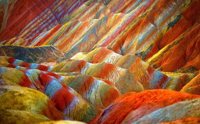 «Полосатые» горы геологического парка Данься словно сошли с полотна импрессиониста: настолько щедро природа одарила их из своей палитры. Красный, оранжевый, желтый, белый, голубой, зеленый — разве на Земле скалы бывают таких цветов? Горы примечательны и своими формами: они чрезвычайно разнообразны, много необычных возвышений, гротов, пещер, оврагов. В одиночку по ним ходить опасно, поэтому осмотреть заповедник можно только в составе организованной группы. Билеты продаются прямо на въезде. Путь из крупных городов Поднебесной вроде Шанхая и Пекина до провинции Ганьсу неблизкий, но дело того стоит. Лучшее время для посещения — лето.