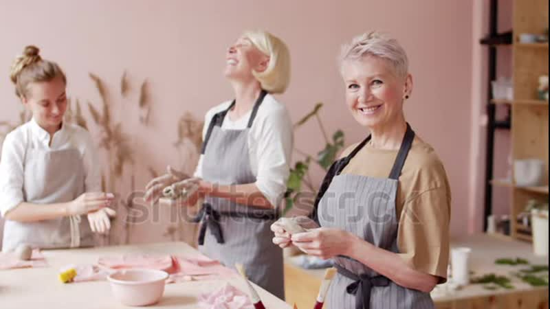 Stock footage panning of middle aged caucasian woman with short haircut standing at worktop holding clay lump in