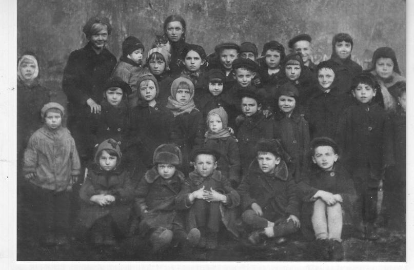 Фотография детей нашего двора. На ней я слева во втором ряду, третья, а первая с забинтованной головой – средняя сестра Мария. Старшая сестра Ольга в третьем ряду первая, самая высокая. Здесь же на этой фотографии два двоюродных брата и есть другие дети, что умерли от голода в 1941– 1942 годах. Снимок сделан в мае 1941 года. Боровая улица, дом № 100